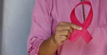 Une femme en rose qui tient un noeud rose